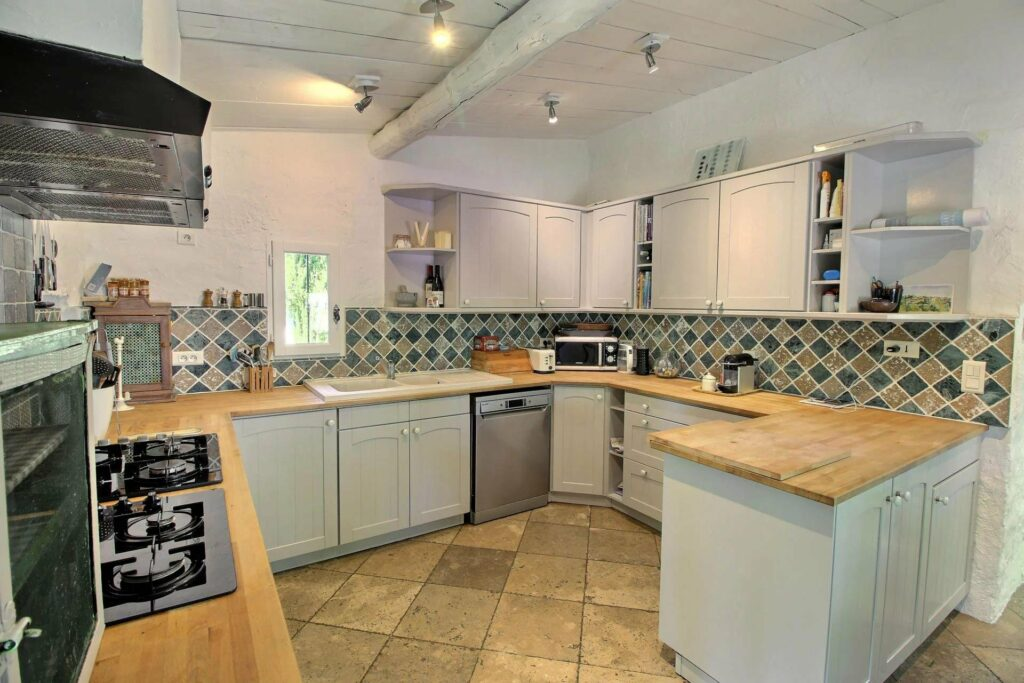 french style kitchen with white cabinets and tile design backsplash with wood countertops at south france property