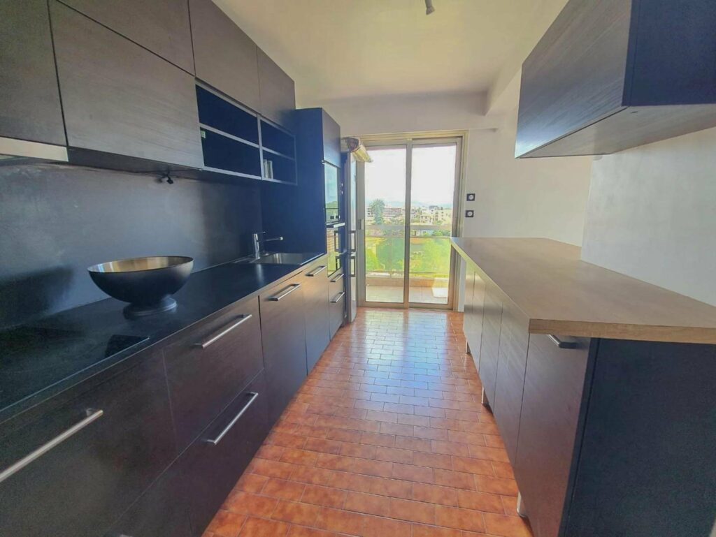 kitchen with dark brown cabinets and access to terrace through sliding glass door