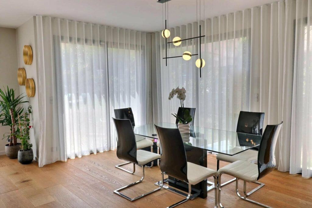 dining room with modern glass table and black sleek chairs