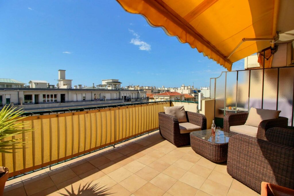 terrace high up with a view of the mediterranean sea with tile floors and brown outdoor furniture
