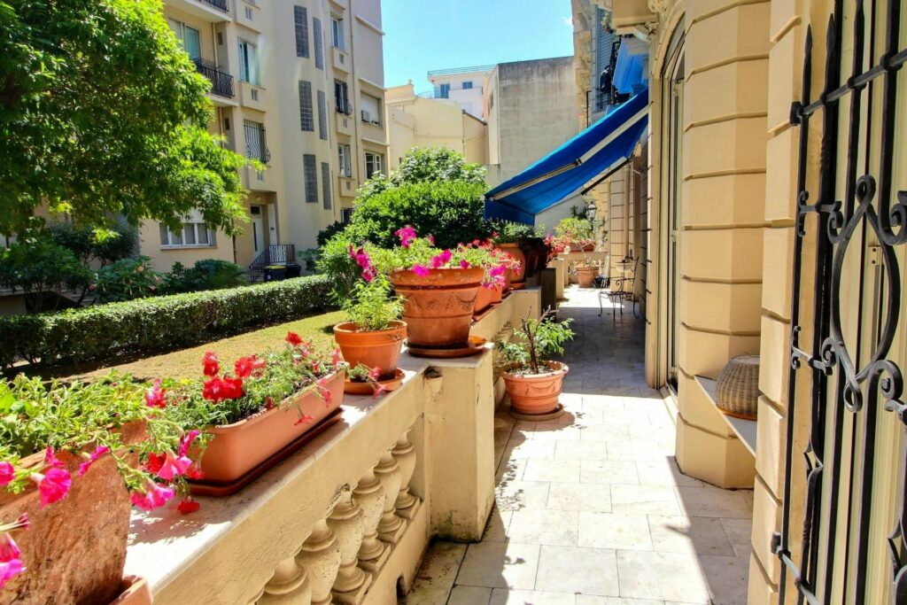 large terrace of bourgeois apartment in nice with red flowers in in flower pots south france