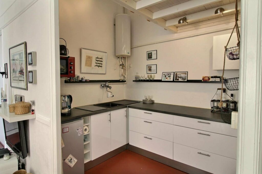kitchen of apartment in menton old town with white cabinets and black marble counter tops