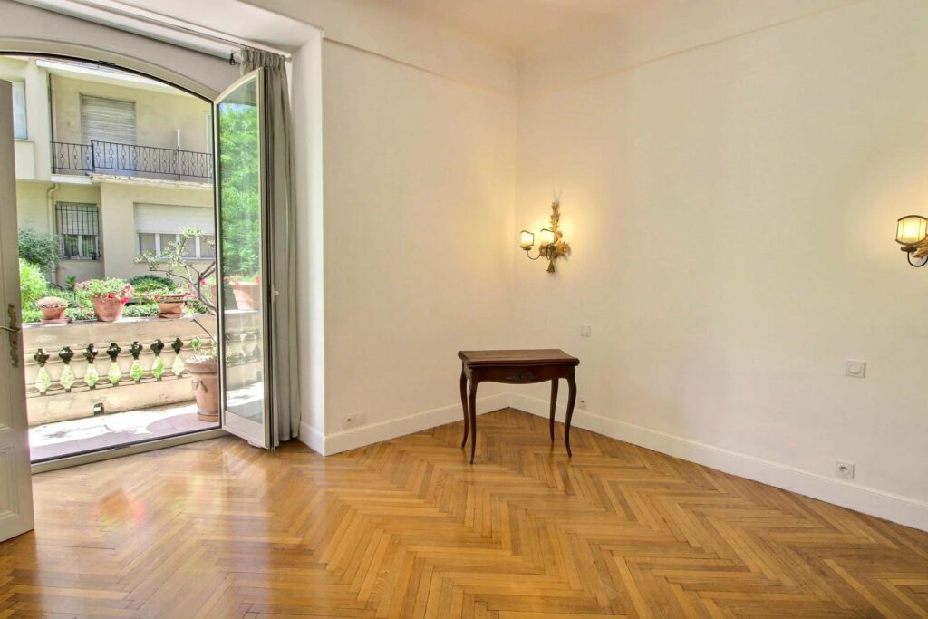 large room with chevron printed wood floors and small wood table in corner of white walls with yellow lamp above