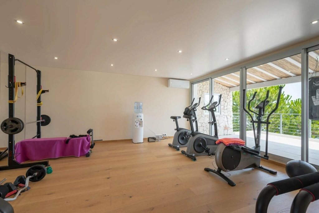 open room with hree exercise machines and wood floors with sea view
