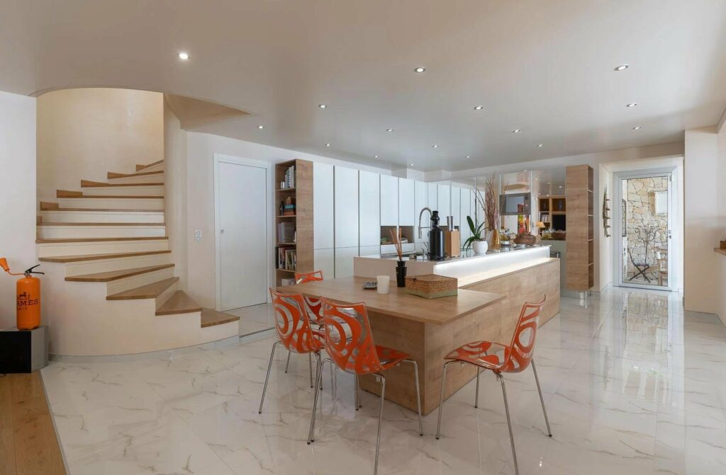 kitchen and dining room of luxury villa in south france with orange chairs and white theme