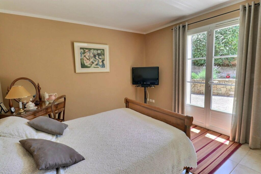 bedroom with double bed with wood bed frame and tv in corner of room with large french doors access to backyard