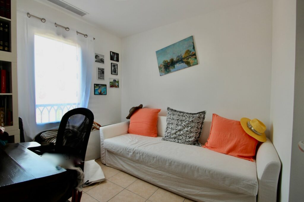 seating area with white couch and orange and blue accents pillows with painting above