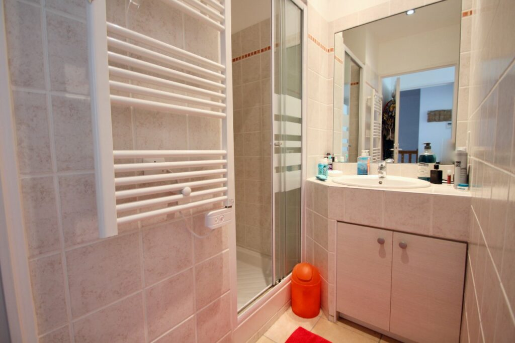 small bathroom with white cabinets and tiling