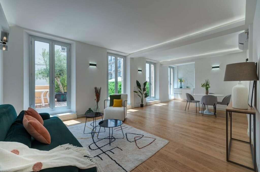 large open living room with wood floors and large glass doors leading to terrace