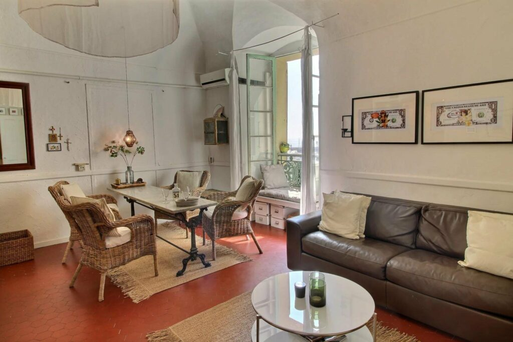 living room of apartment in menton old town with brown leather couch and charming decor