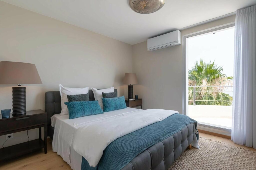 modern bedroom with teal and white colored bedding and terrace