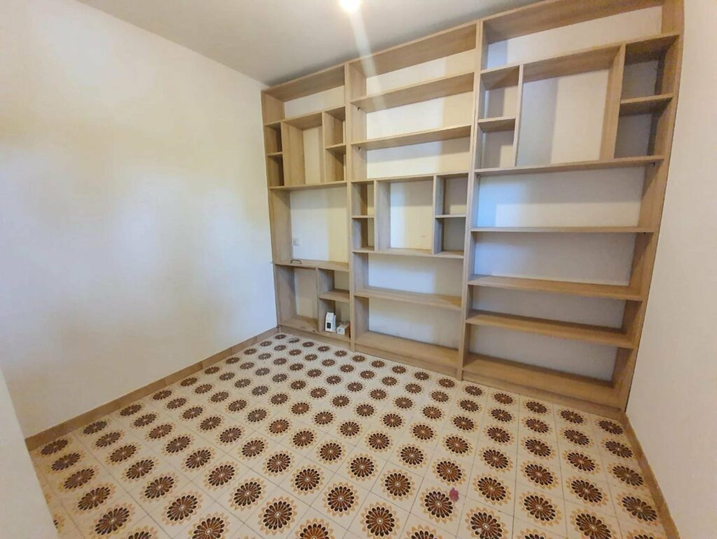 walk in closet of light with printed tile floors