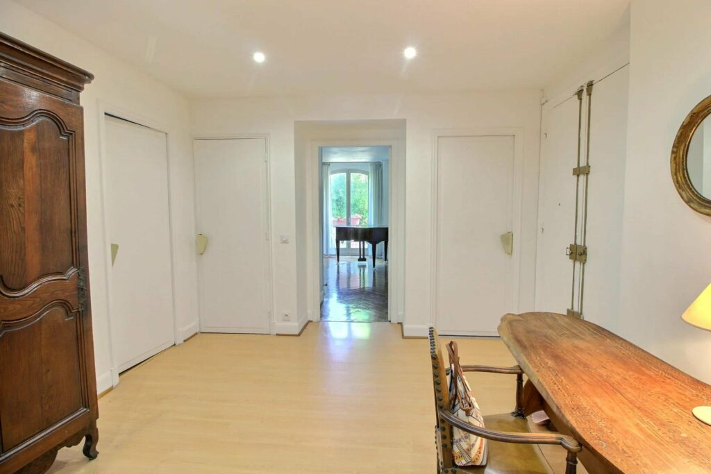 open room with light wood floors and wood table surrounded by white walls