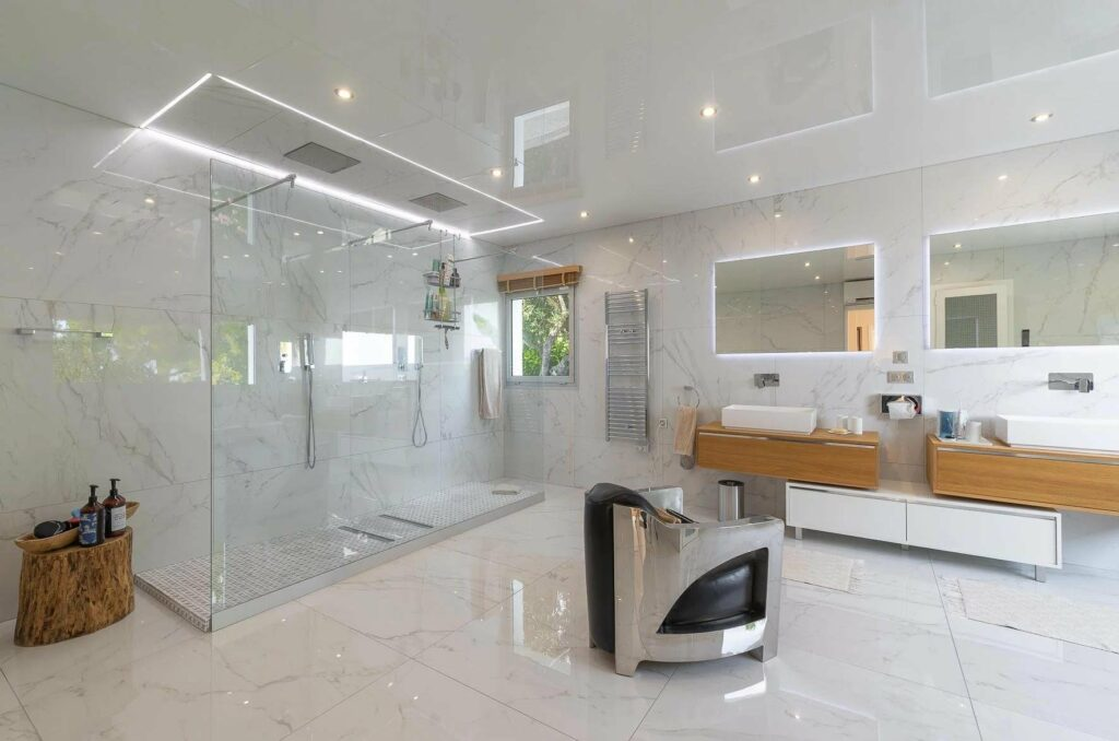luxury bathroom with large glass shower and marble walls and floors