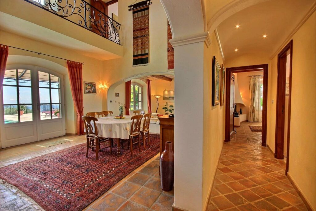 dining room in house in grasse with red rug under large table