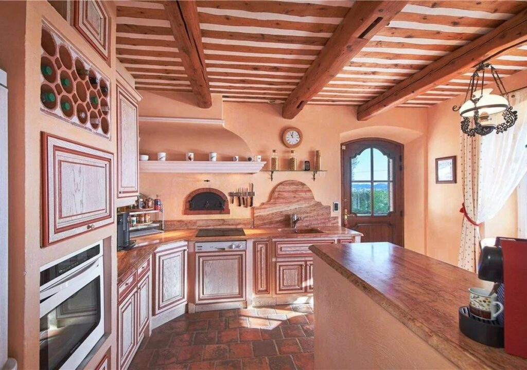 provencal kitchen with exposed wood beams and light teracotta walls
