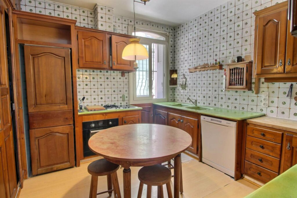 kitchen with with wood cabinets and light green tile walls with round wood table in center