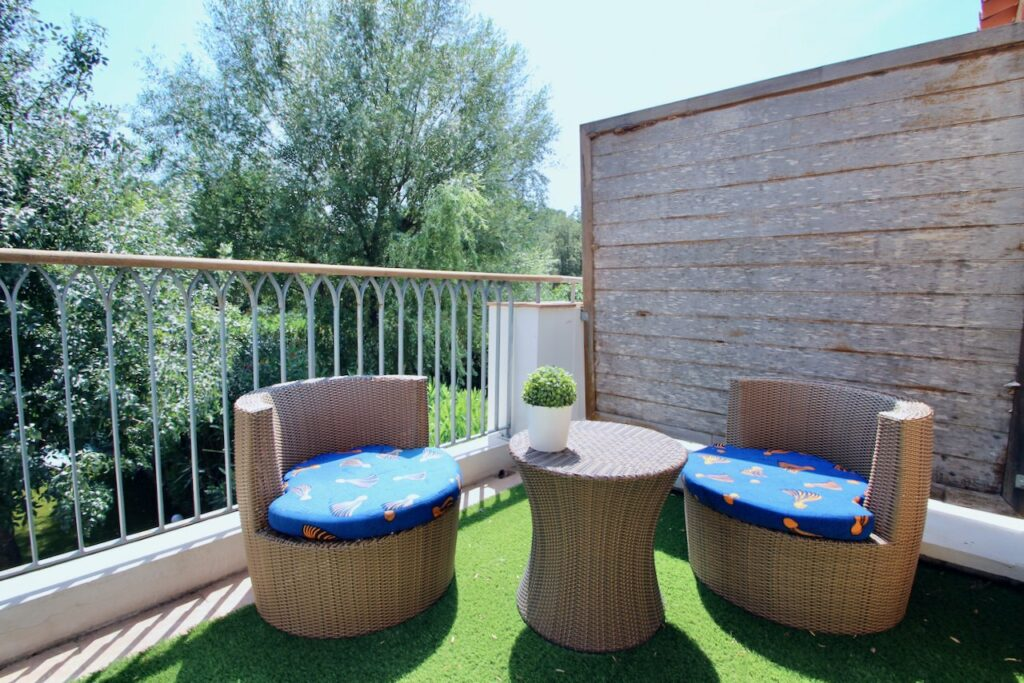 outdoor deck with two lounge chairs and green grass floors overlooking garden