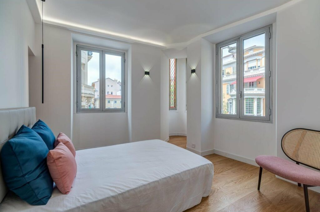 bedroom with white bedding and pink accent pillows at apartment in nice