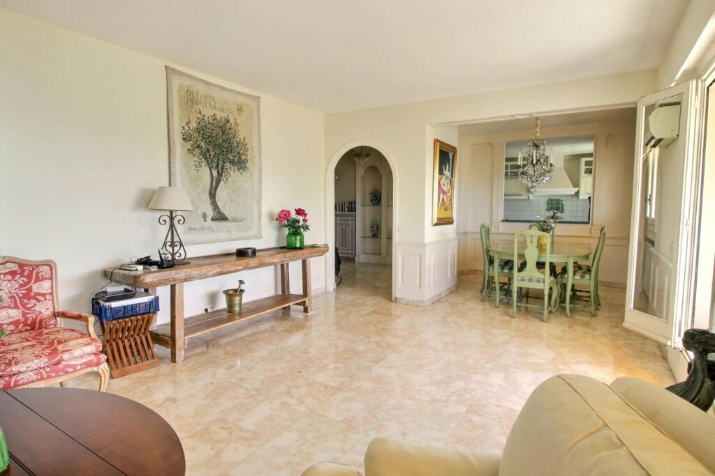 living room of apartment white tile floors and round archway and chic decor