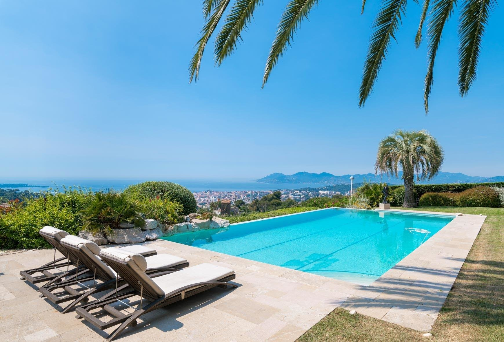 backyard of luxury villa with large pool overlooking city of cannes and sea