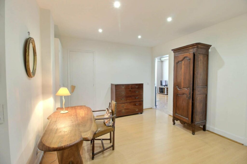 office with dark wood table chair closet and dressor surrounded by white walls and light wood floors