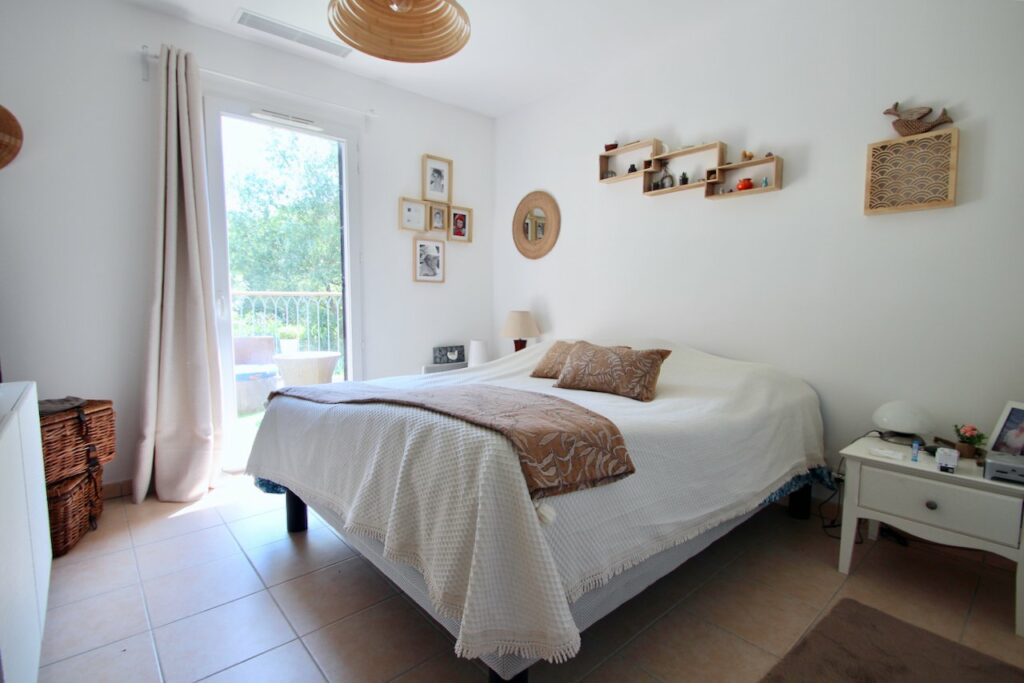 bright bedroom with white bedding and access to outdoor deck