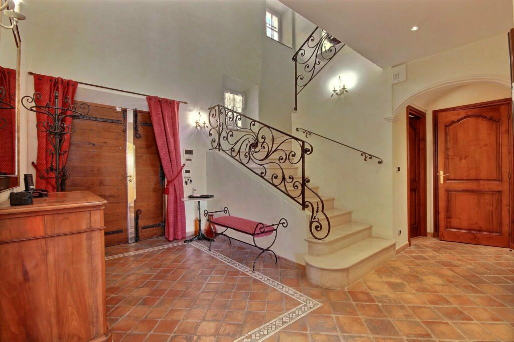 entrance to mas in grasse with tile design floors with high ceilings and stairs leading up to bedrooms