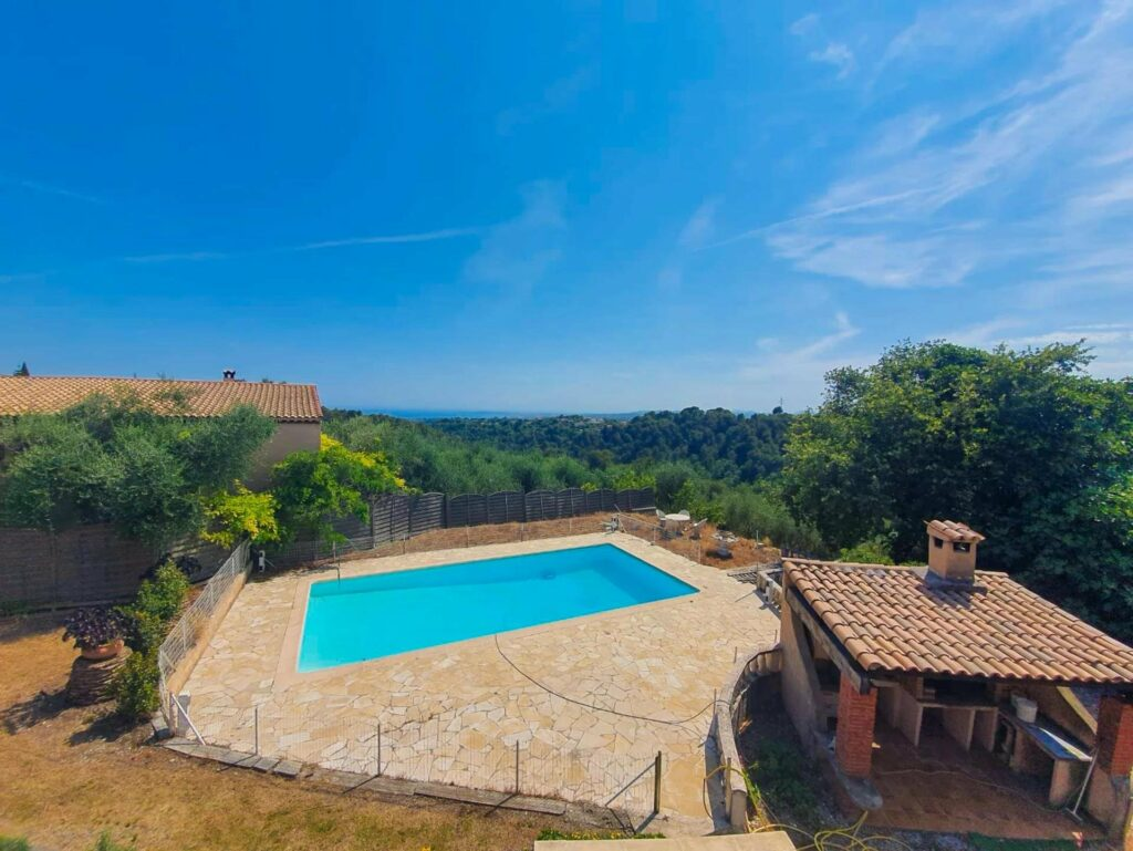 backyard of house in southern france with large pool and view of surrounding hills and mountains