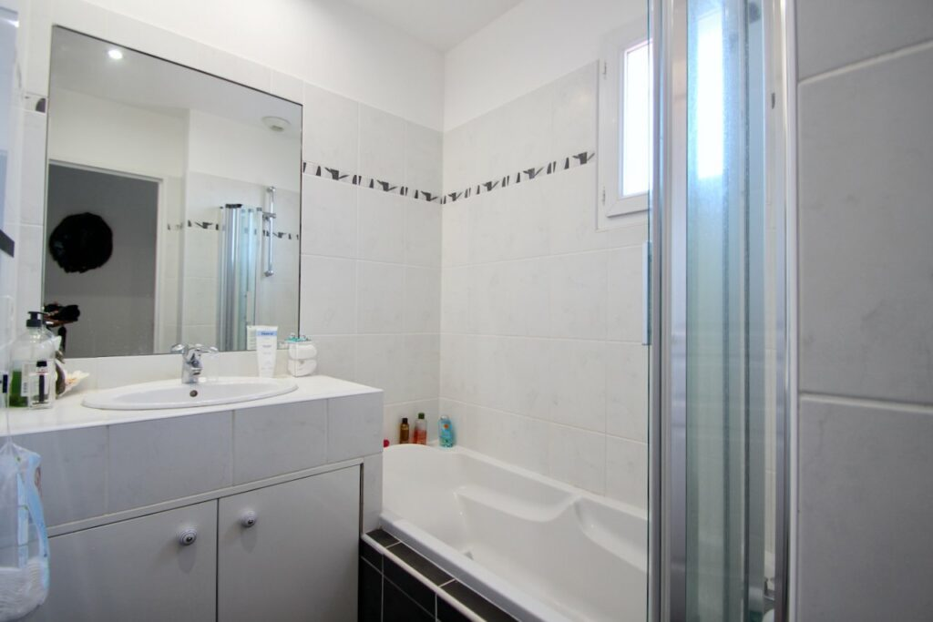 bathroom with white bath tub and white cabinets