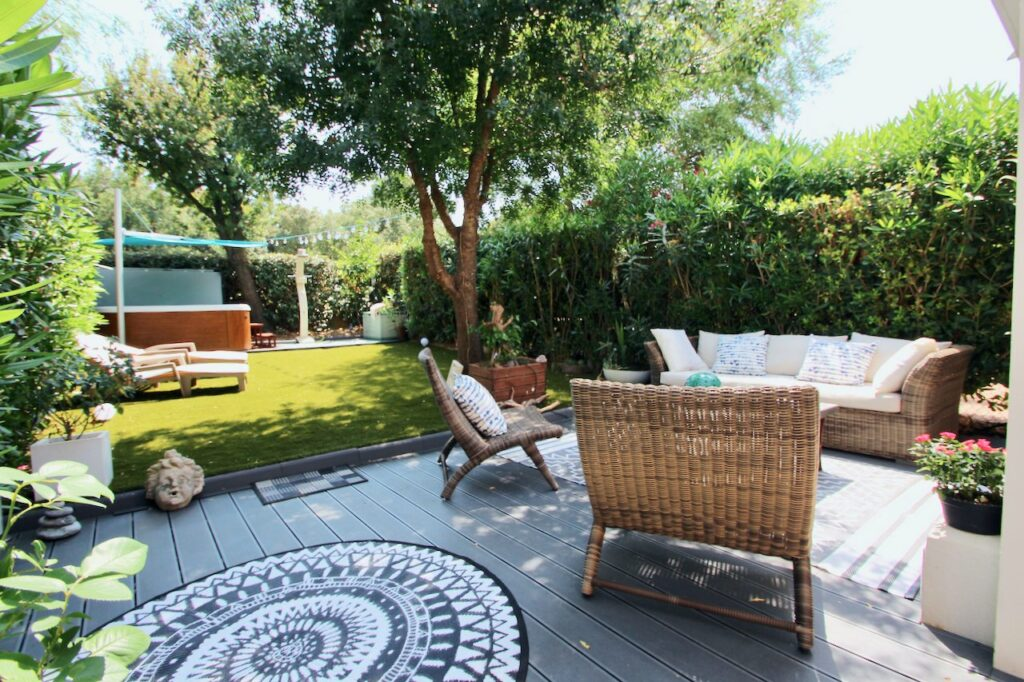 backyard of home in southern france with outdoor furniture and printed tile floors