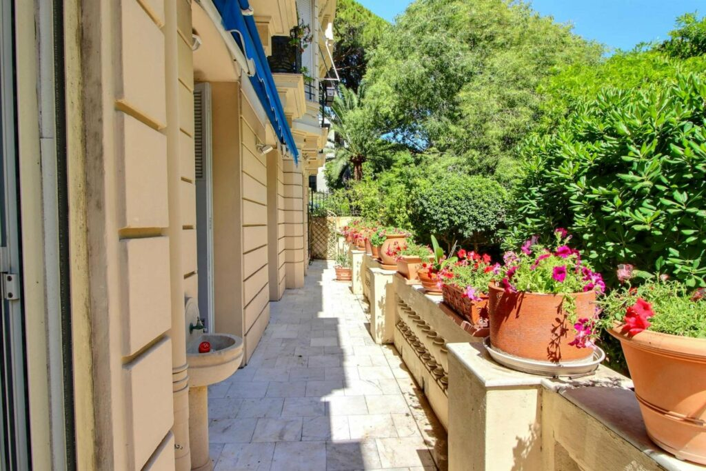 long terrace on side of apartment on ground floor with view of greenery and red flowers