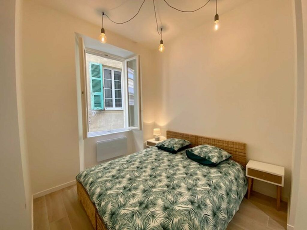 modern renovated bedroom with leaf printed bedspread with open french door windows facing apartment building with blue shutters