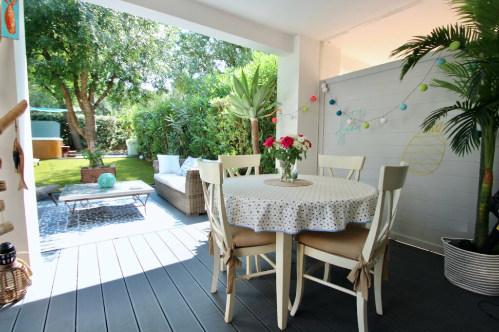 outdoor sitting area with white table on wooden deck