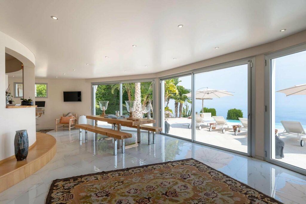 dining room view with colorful rug and large sliding glass door to terrace with sea view