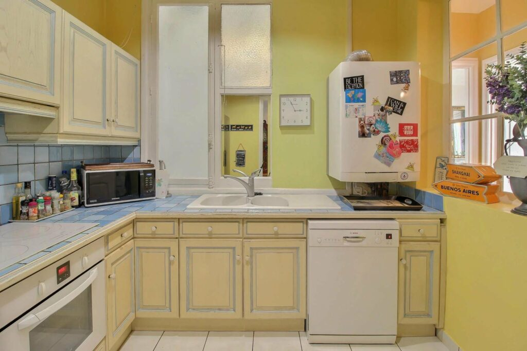 retro kitchen with yellow cabinets and wall and white appliances