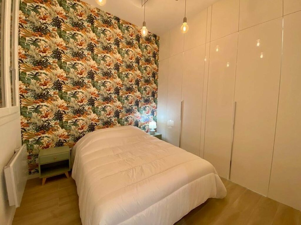 bedroom with colorful wallpaper behind white full size bed