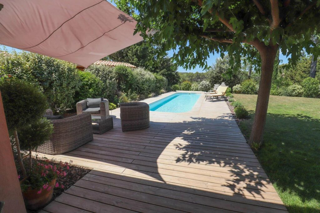backyard of villa with long pool and wooden deck with layout chair