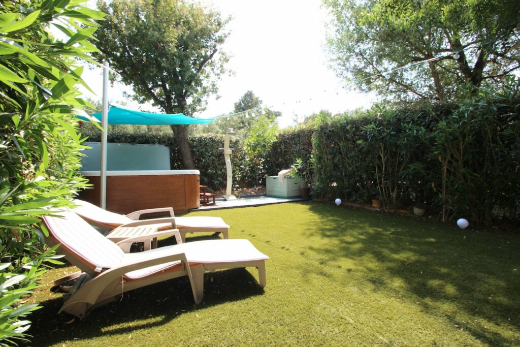 backyard with home in france with bright green trees and two lounge chairs