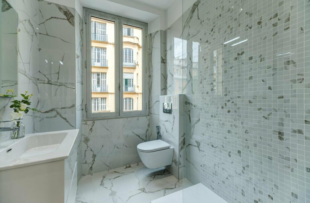small modern bathroom with marble tile floors and walls and window facing surrounding apartment buildings