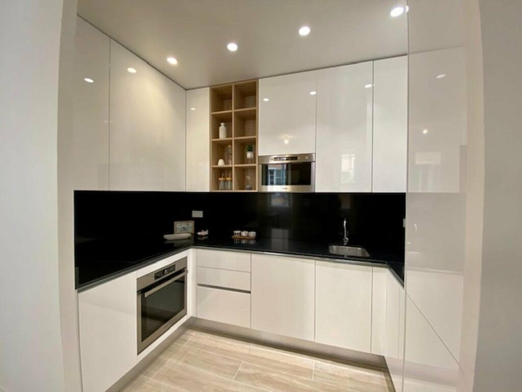 modern kitchen in apartment in nice with black countertops and backdrop with white cabinets