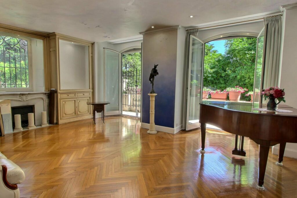 beautiful living area of apartment in nice with wood floors and grand piano