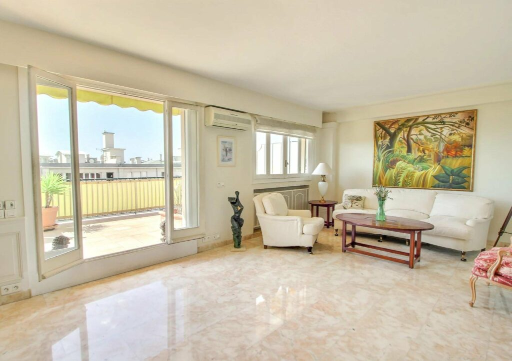 living room with white tile floors and large glass sliding door to terrace with white couch