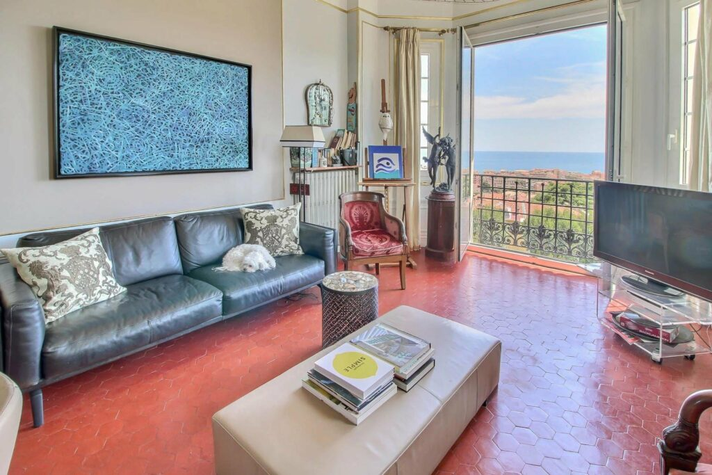 living room at menton apartment with leather couch and red floors with large sea view terrace