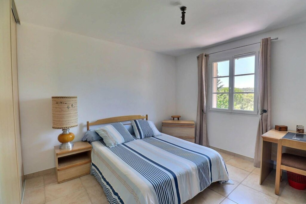 bedroom with double bed white blue and white bed spread with small window next