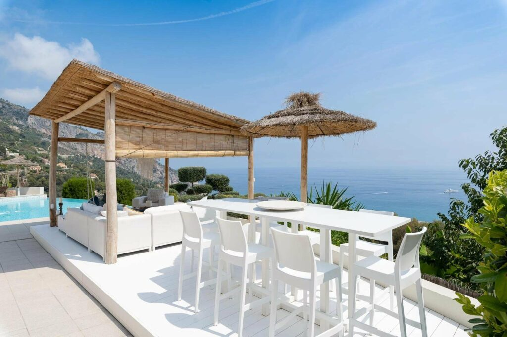 backyard with white table and chairs with sea view