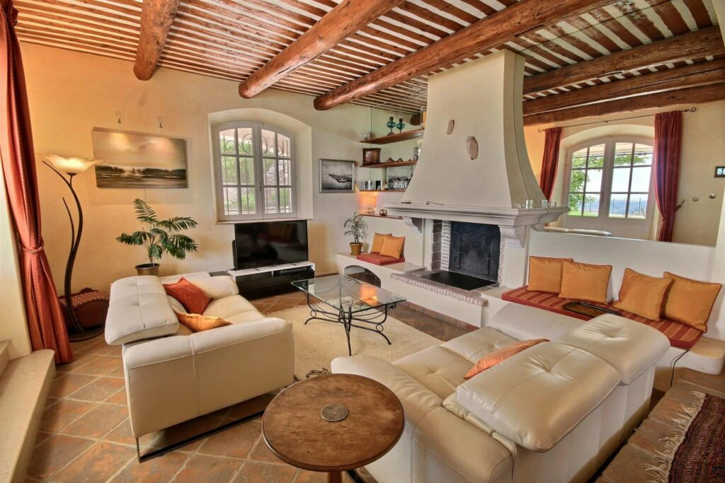 living room with white couch and high ceilings with exposed wood beams and modern fireplace