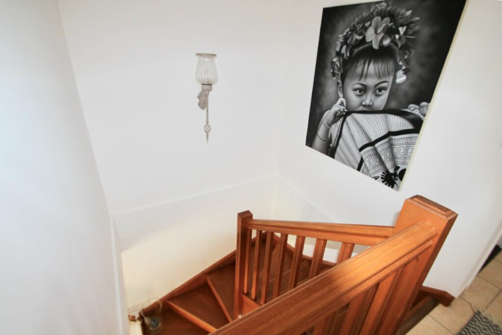wooden stairway with black and white painting of young girl