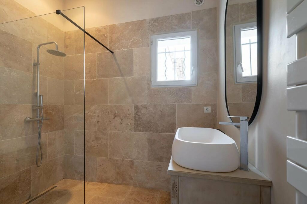 bathroom with brown tile walls and white sink next to window