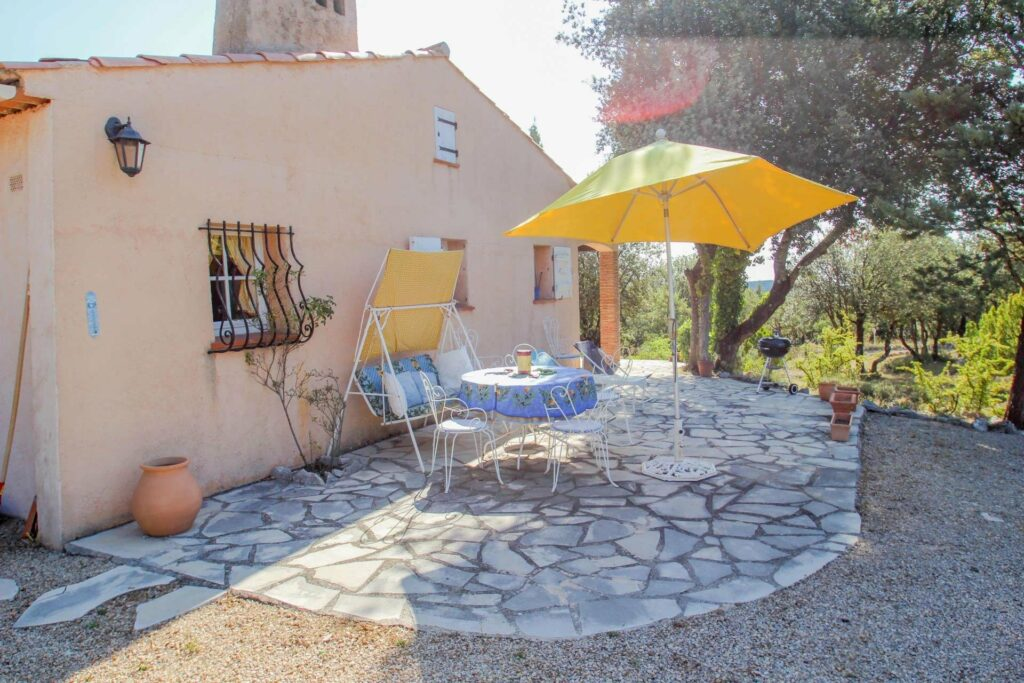 patio of provencal house with yellow umbrella